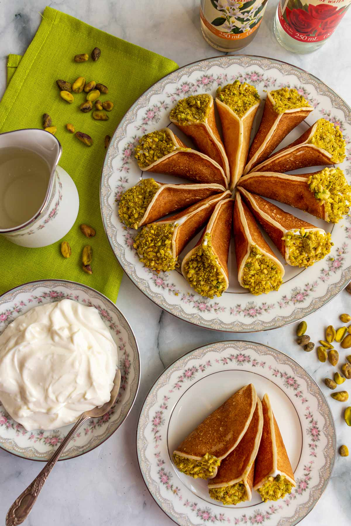 Two plates of atayef, a bowl of ashta cream, pitcher of syrup and scattered pistachios.