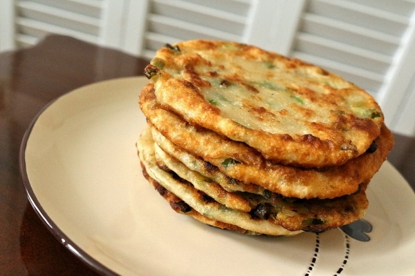 side view of a stack of Chinese scallion pancakes on a plate