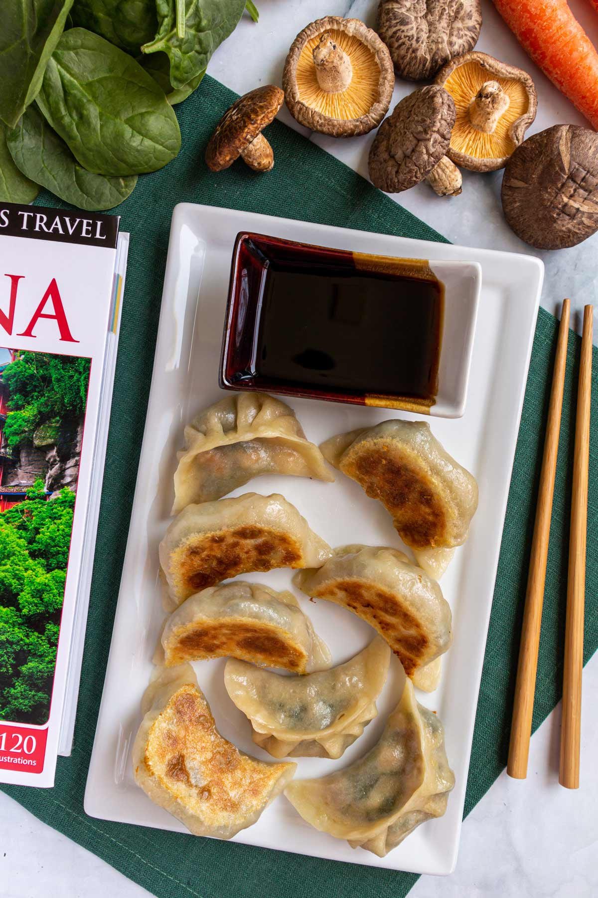 A plate of potstickers, a China travel book, chopsticks, mushrooms, and spinach on a green napkin.
