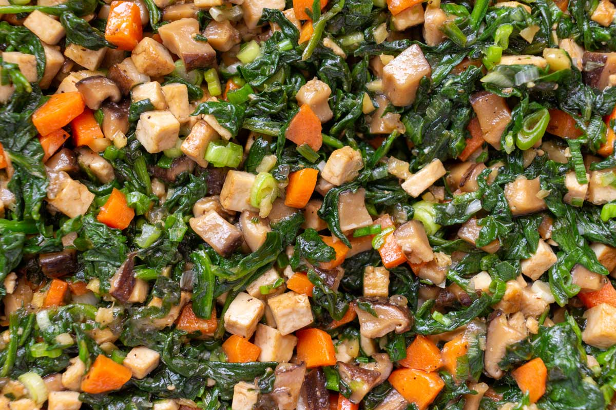 Closeup of vegetarian dumpling filling made with spinach, carrots, mushrooms, and tofu.