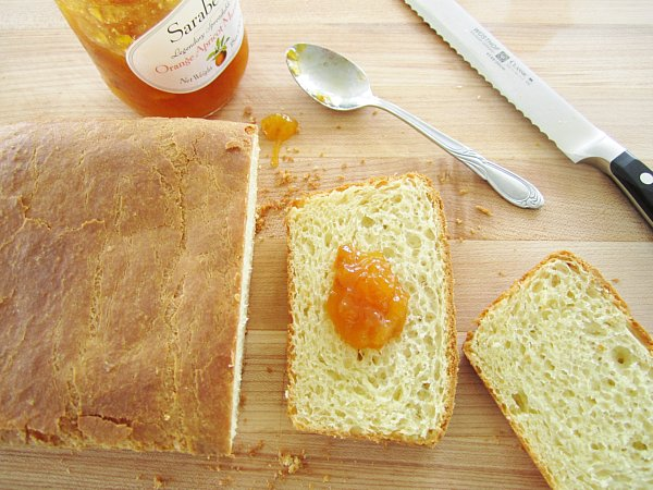 overhead view of a partially sliced loaf of brioche with orange jam on one slice