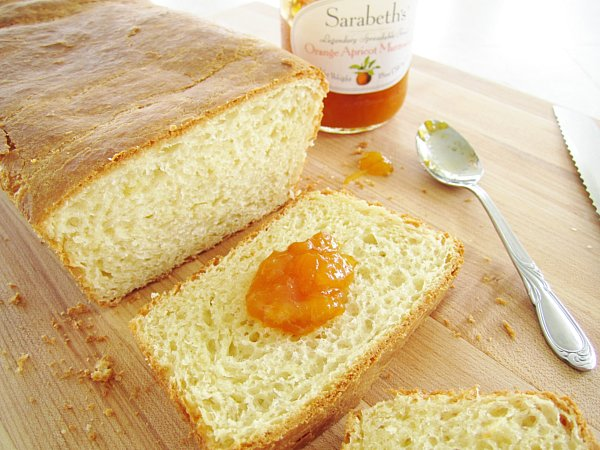 a partially sliced loaf of brioche with a dollop of orange marmalade on one slice