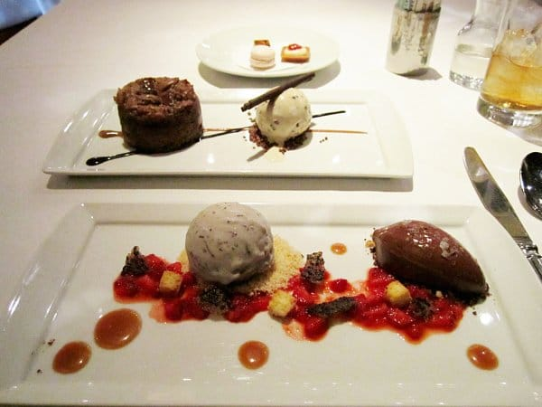 two plates of artistically plated desserts on a white tablecloth