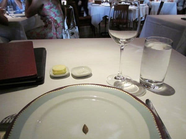 A table setting in a restaurant with a plate, utensils, and glasses on a white tablecloth