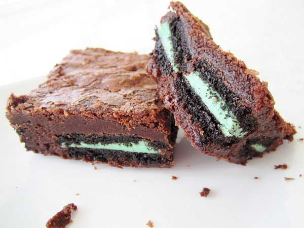 side view of two brownies stuffed with mint Oreos on a white plate