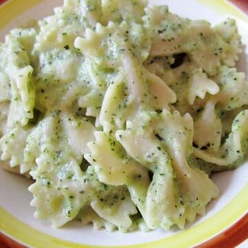 a closeup of a bowl of farfalle pasta with light green zucchini sauce