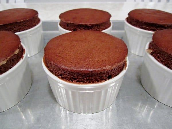 chocolate souffles in white ramekins on a metal baking sheet