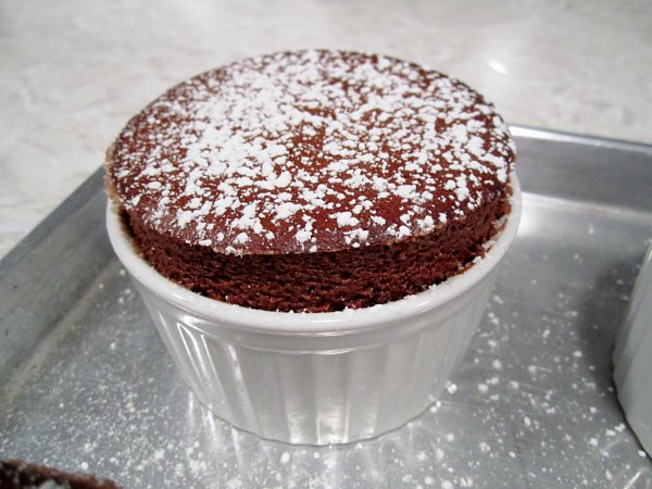 a closeup of a chocolate souffle dusted with powdered sugar in a white ramekin