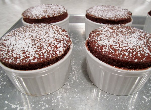 four chocolate souffles dusted with powdered sugar on a metal baking sheet