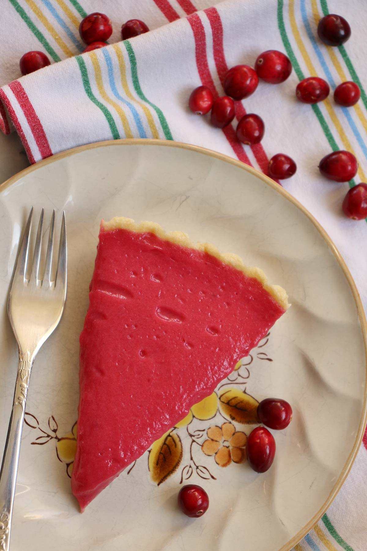 A slice of cranberry curd tart on a plate with a fork and fresh cranberries.