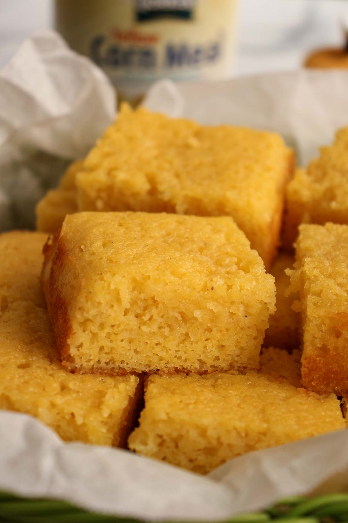 Closeup of a square of cakey honey butter cornbread piled into a green basket.
