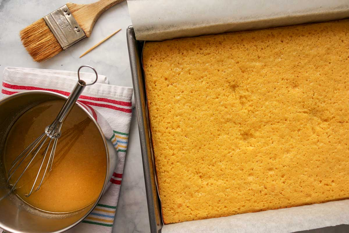 A saucepan of honey butter glaze next to a rectangular pan of cornbread.