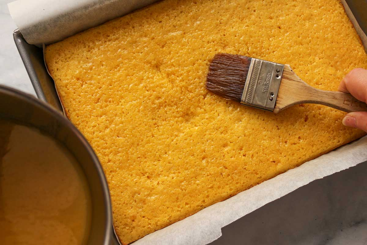 A wide brush applying honey butter glaze to the top of a pan of cornbread.