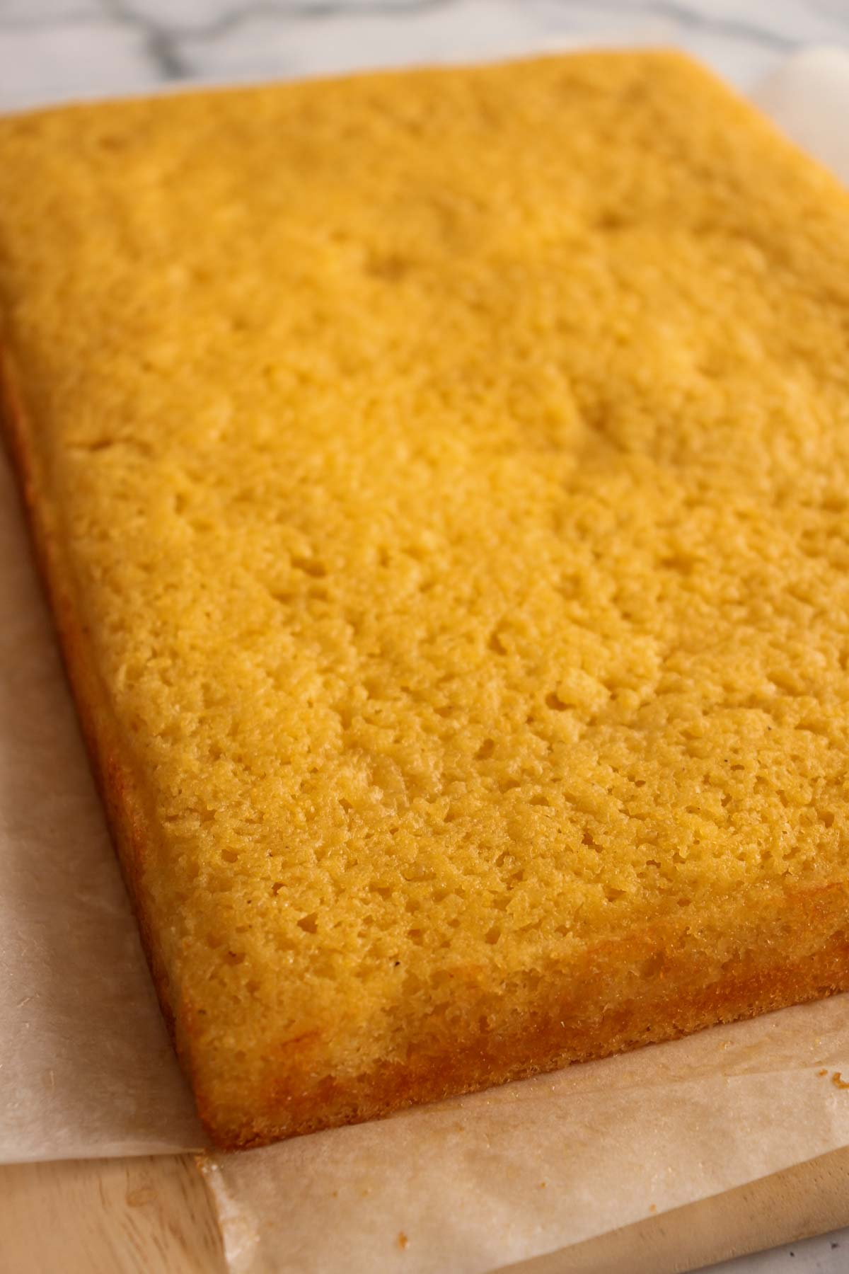 A rectangular slab of baked cornbread with parchment paper beneath it on a wooden board.