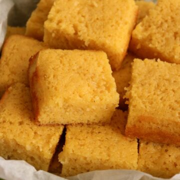 Closeup of squares of honey butter glazed cornbread piled on top of each other.