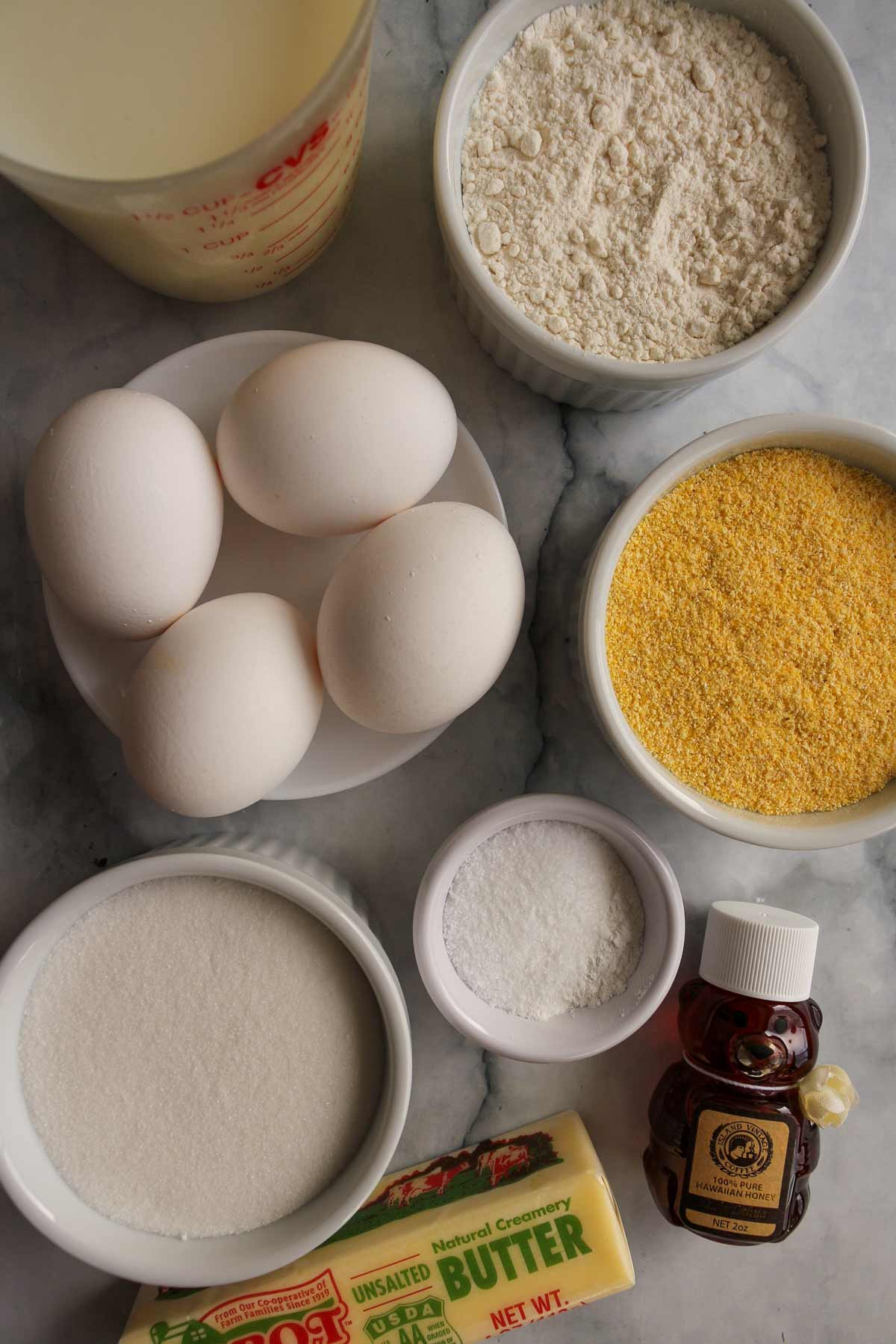 Milk, flour, eggs, cornmeal, sugar, salt, baking powder, honey, and butter.