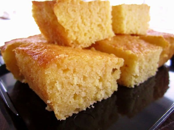 a closeup of a pile of corn bread squares on a black surface