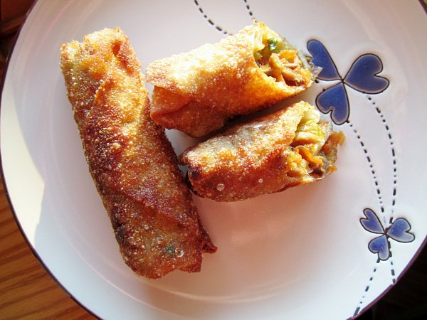 overhead view of a plate of egg rolls with one cut in half