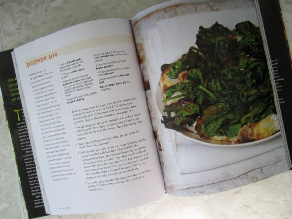 snapshot inside a cookbook with a recipe and a photo of pizza topped with spinach