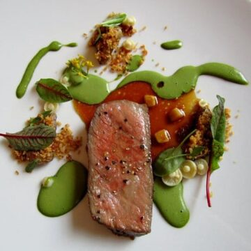 overhead view of a slice of steak surrounded by tiny mushrooms and green sauce drizzle