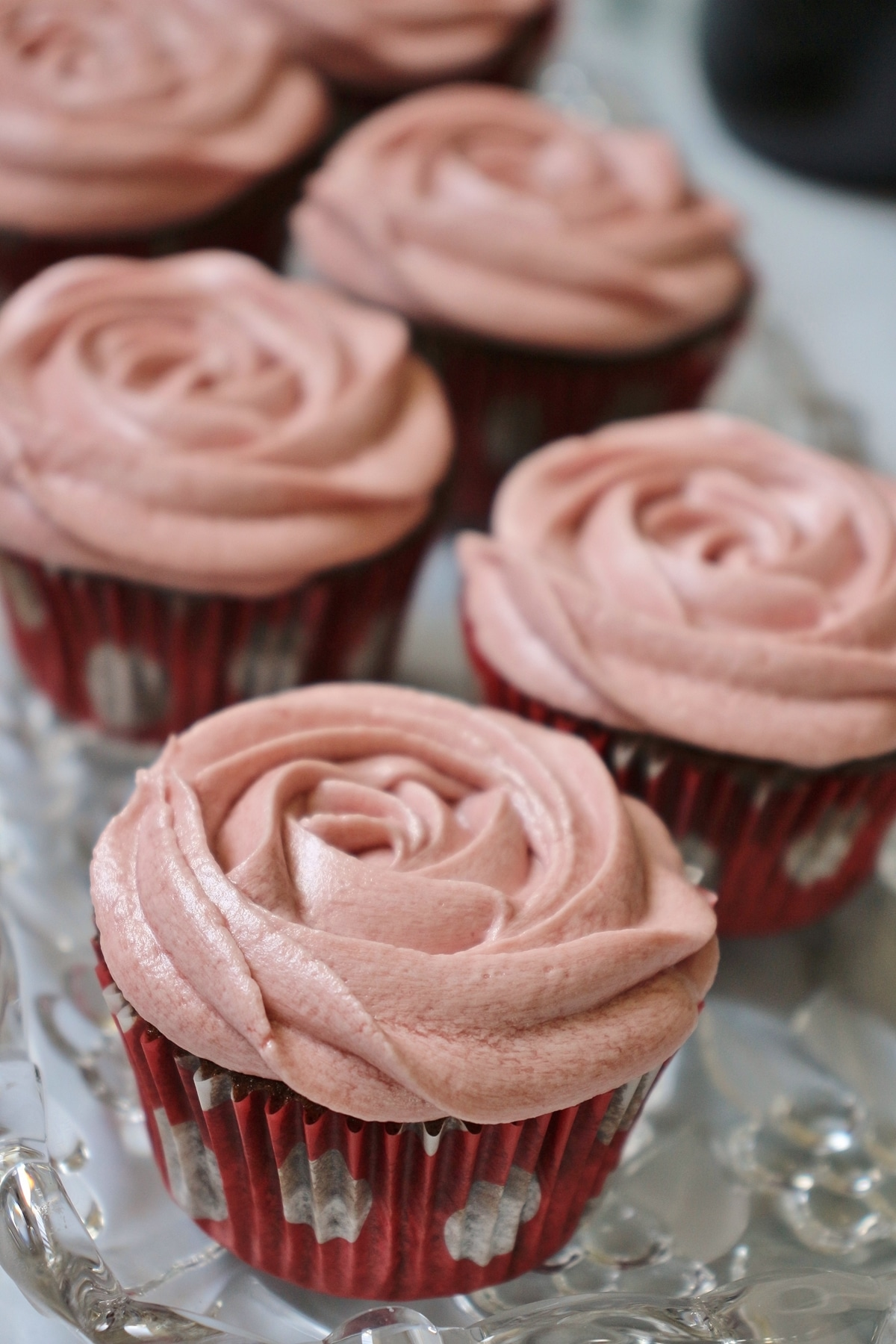 6 chocolate cupcakes with red wine buttercream frosting on a glass tray