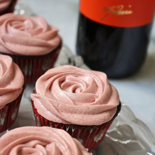 chocolate cupcakes with red wine frosting on a glass tray, with a bottle of red wine