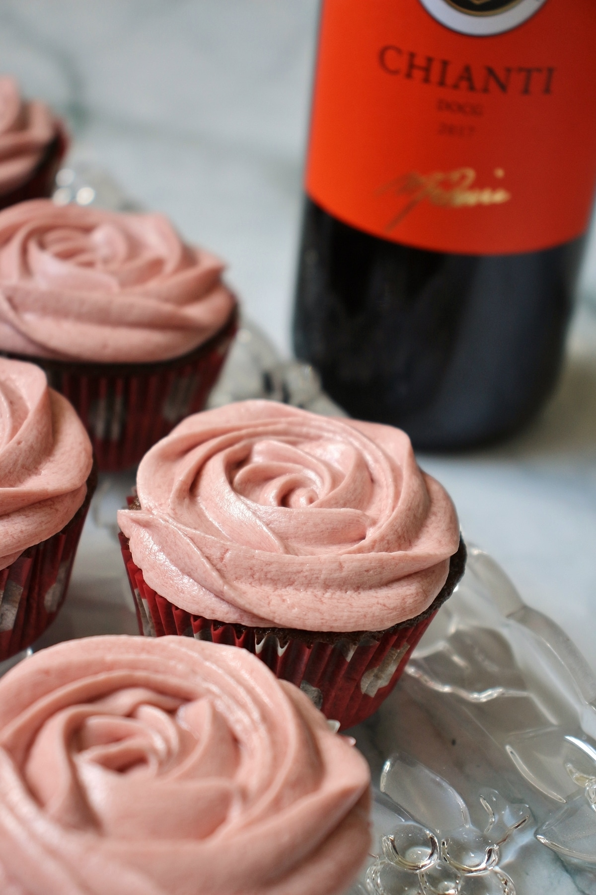 chocolate cupcakes with red wine buttercream, and a bottle of wine in the background