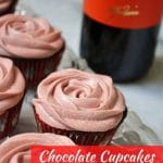 cupcakes with pink frosting and a bottle of wine in the background
