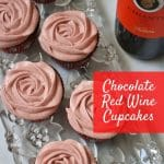 overhead view of 6 cupcakes with pink frosting, next to a bottle of wine