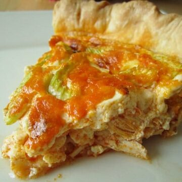 closeup of a slice of buffalo chicken quiche on a white plate
