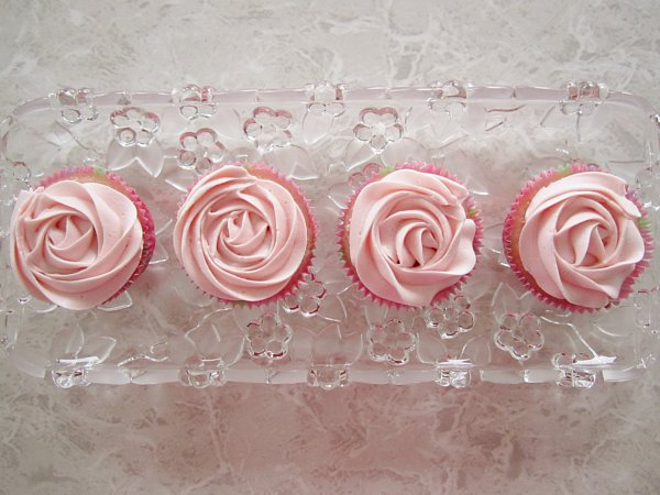 overhead view of a row of cupcakes with pink frosting that resembles a rose