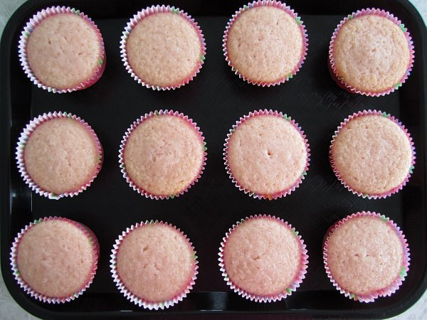 overhead view of pink cupcakes on a black surface