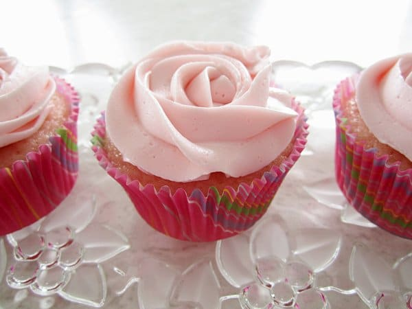 a closeup of a pink lemonade cupcake with pink frosting that resembles a rose