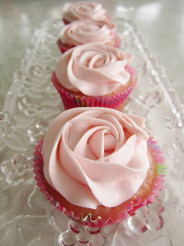 a row of cupcakes with pink frosting that resembles a rose arranged on a glass tray