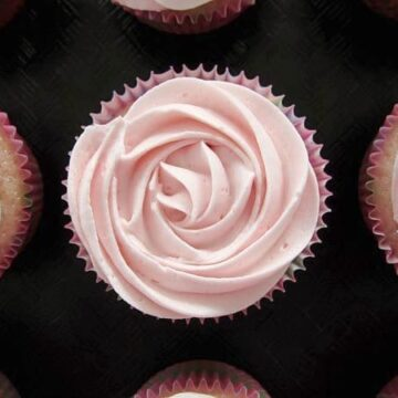 overhead closeup of a cupcake on a black surface with pink frosting that resembles a rose