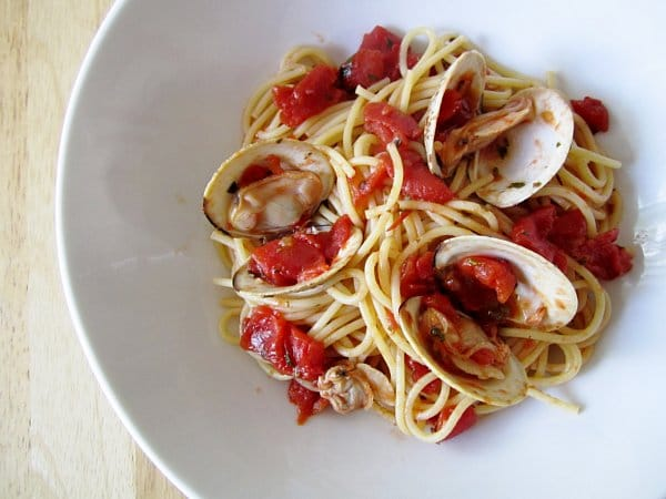overhead view of a wide white bowl filled with spaghetti with red clam sauce