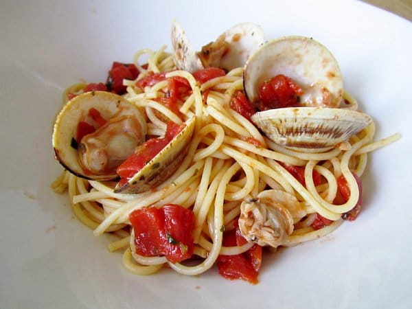 side view of spaghetti with red clam sauce in a white dish