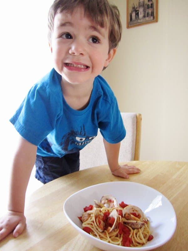 A little boy standing at a table behind a bowl of spaghetti with red clam sauce