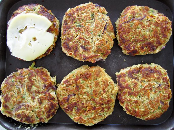 overhead view of six cooked veggie burger patties on a black surface