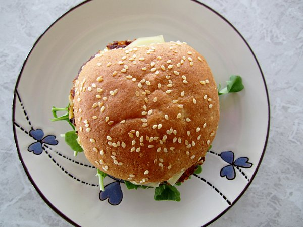 overhead view of a burger with a sesame seed bun on a plate