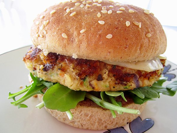 side view of a veggie burger with a sesame seed bun on a plate