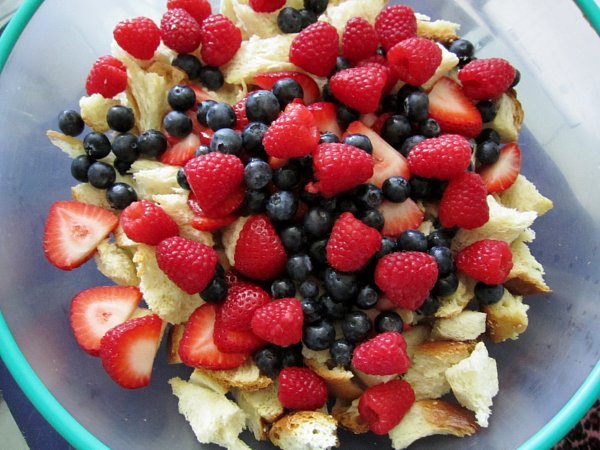 a mixing bowl of cubed bread, blueberries, raspberries, and strawberries