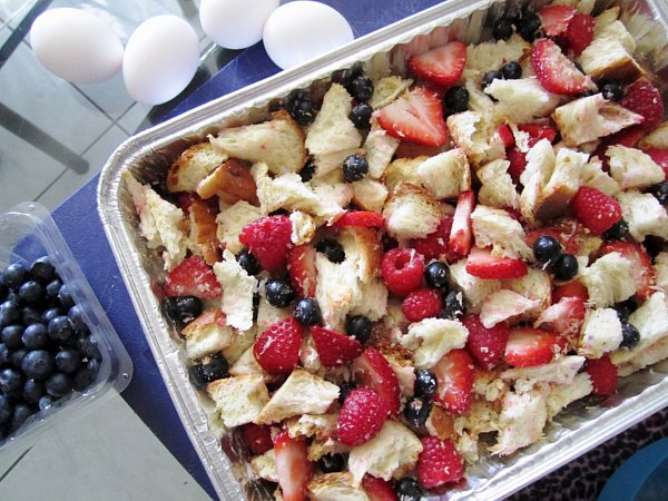 overhead view of a foil tray filled with cubes of bread and berries