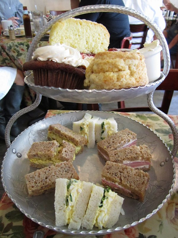 a metal two tiered display of tea sandwiches, scones and sweets