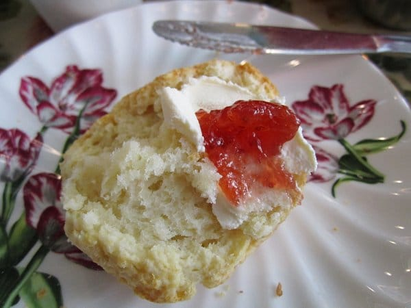 a closeup of a halved scone topped with clotted cream and strawberry jam