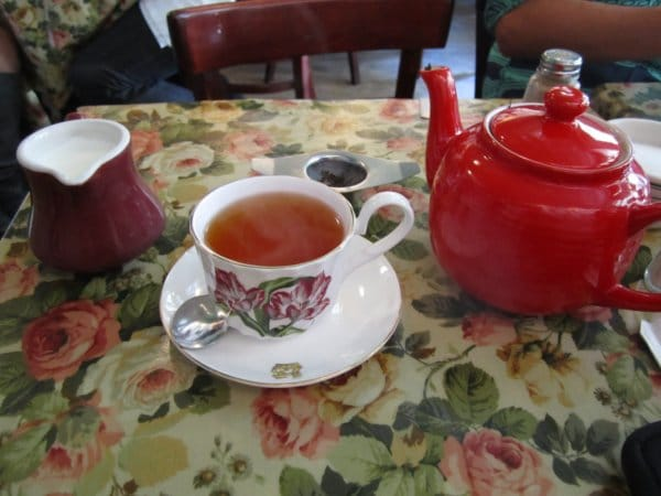 A table topped with a cup of tea and a red ceramic tea pot