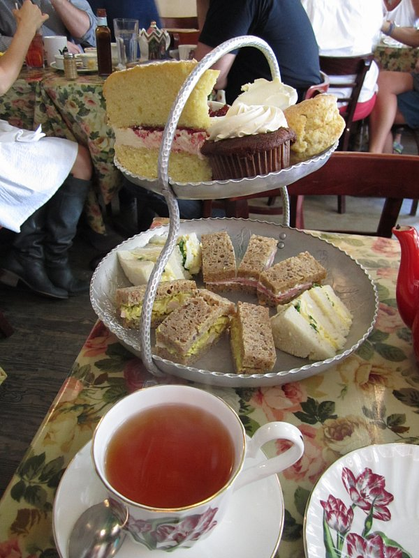 a cup of tea in front of a two-tiered afternoon tea display of sandwiches and sweets