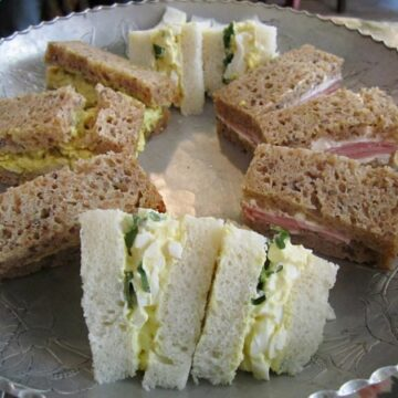 A closeup of tea sandwiches arranged in a circle on a metal surface