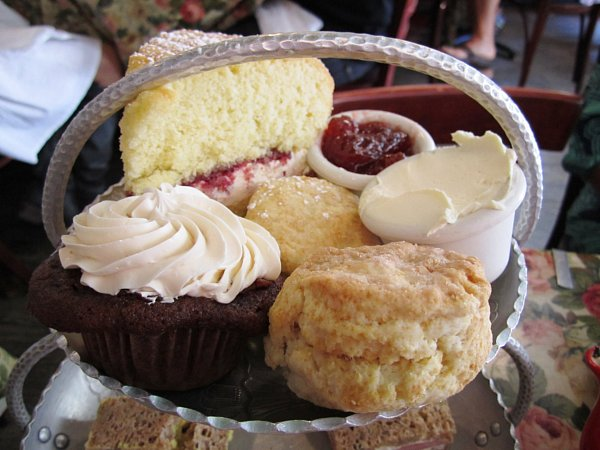 a closeup of scones, cakes, jam and clotted cream on a metal surface