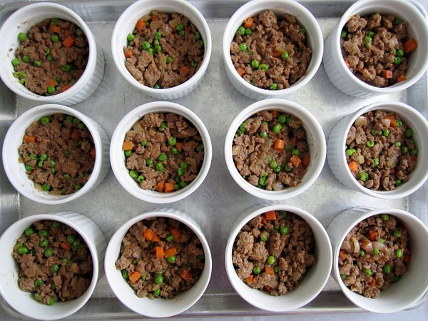 Individual cottage pies / shepherd's pies in ramekins minus the mashed potato topping. The cooked ground beef filling is visible and also contains peas and carrots. The ramekins are lined up on a baking sheet mid-assembly.